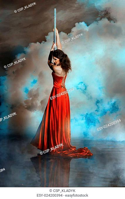 Girl shrouded in smoke holding on to pole dance