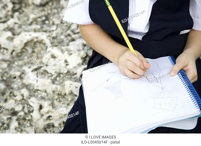 A schoolgirl writing in a notebook
