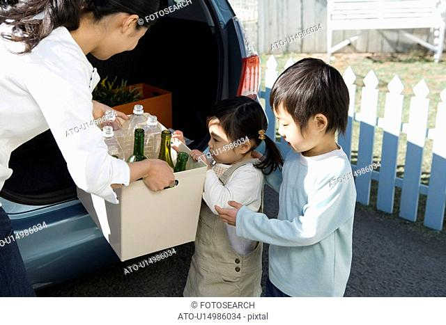 Mother, Girl and Boy Carrying Recycling Bottles into Car