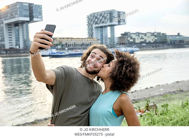 Germany, Cologne, happy couple taking a selfie at the riverside