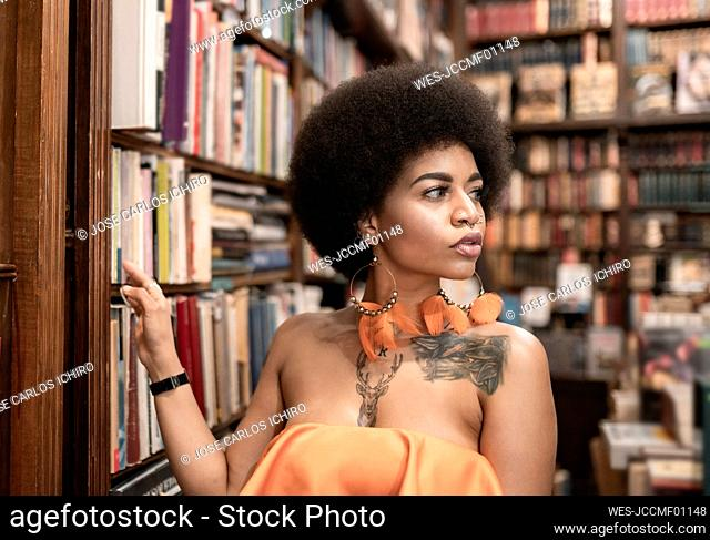 Thoughtful young woman looking away by bookshelf at library