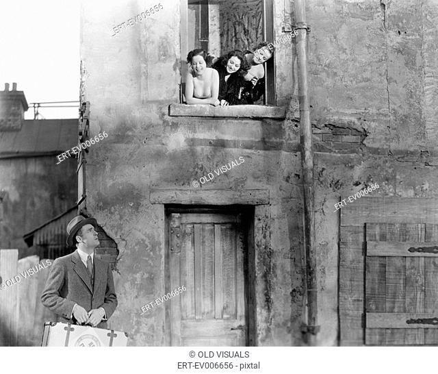 Three women looking out of a window at a man standing in the street with a suitcase All persons depicted are not longer living and no estate exists Supplier...