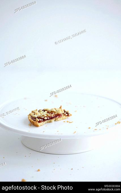 The remains of a damson crumble cake on a cake stand