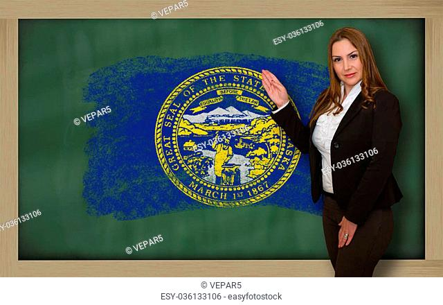 Successful, beautiful and confident woman showing flag of nebraska on blackboard for marketing research, presentation and tourist advertising