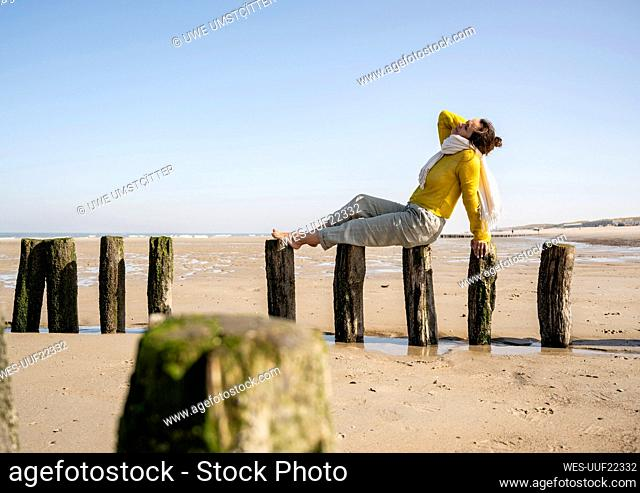 Woman sitting on wooden post at beach against clear sky