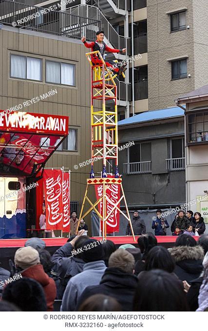 February 11, 2019, Yokohama, Japan - A man climbs stacked chairs during the Lunar New Year celebrations at Yokohama's Chinatown