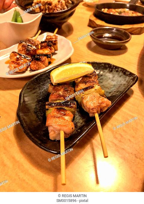 chicken skewers as part of a japanese meal