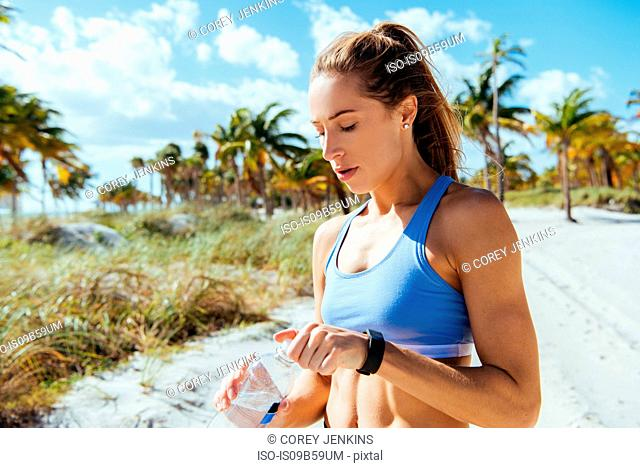Young female runner sitting with bottled water at beach