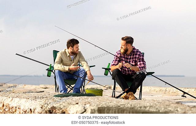 friends adjusting fishing rods with bait on pier