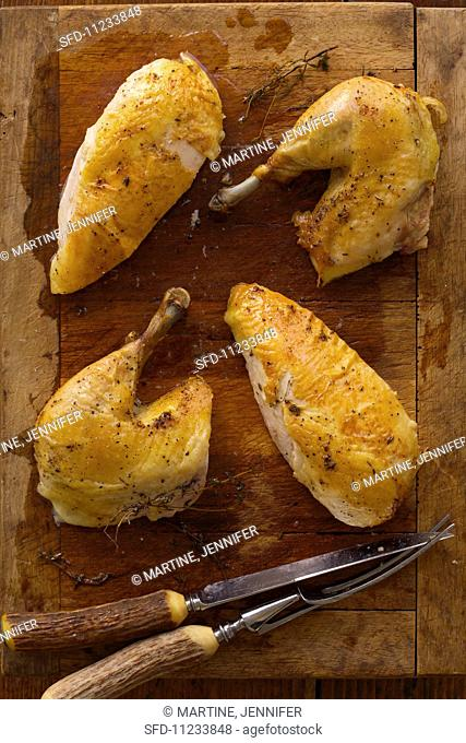 Roasted Chicken Pieces on a Wooden Cutting Board