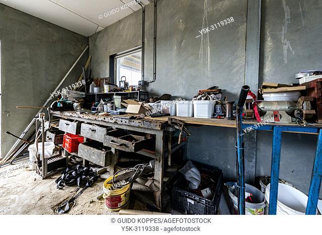 Goirle / Hilvarenbeek, Netherlands. Farmer's workbench and toolroom inside a bull stable