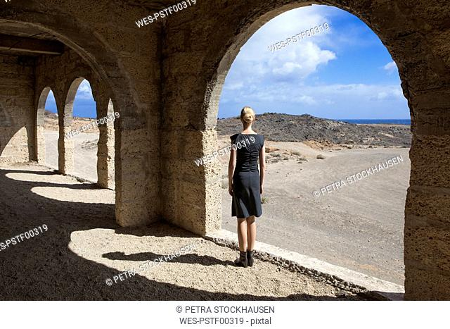 Spain, Tenerife, Abades, Sanatorio de Abona, woman standing at arched window in ghost town building