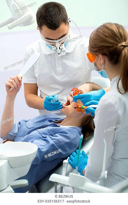 Cute female patient in blue shirt with a mirror in the right hand on the patient chair in the dental cabinet. Next to her there is a male dentist and a female...