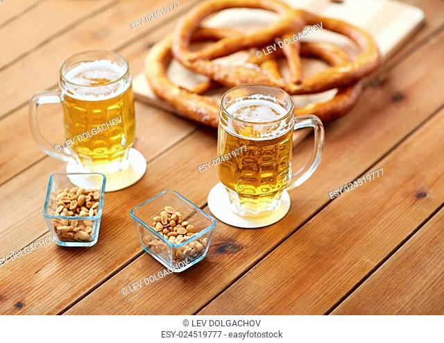 food, baking, cooking and pastry concept - close up of beer in glass, pretzels and peanuts on wooden table at pub