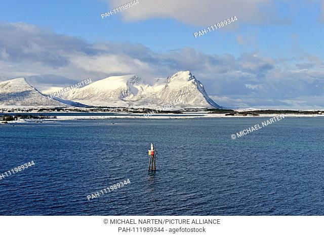 A sea mark in the blue water of the Risøysound in front of the snow white Vesterålen Island Andøya, 10 March 2017   usage worldwide