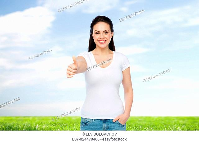advertisement, gesture, clothing and people concept - happy smiling young woman or teenage girl in white t-shirt showing thumbs up over blue sky and grass...