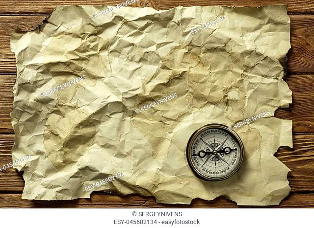 Old crumpled paper and compass on wooden table