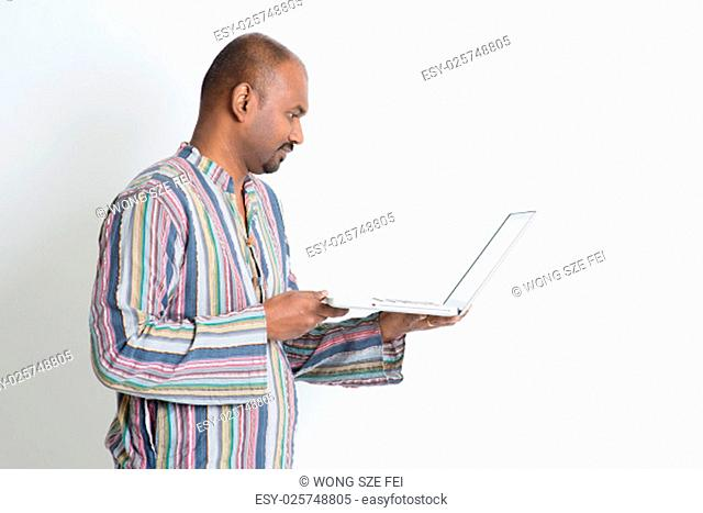 Side view of mature casual business Indian man using laptop computer, looking at pc screen, standing on plain background with shadow