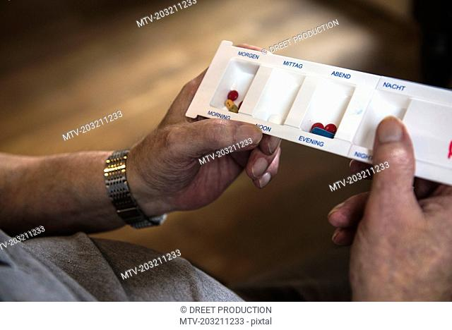 Close-up of hands of senior man with tablet dispensers