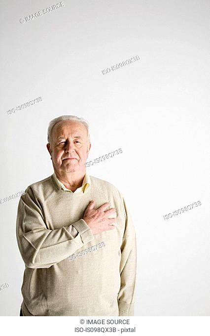 Senior man with hand on heart