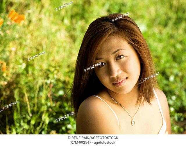 Portrait of an Asian young woman in a field or garden
