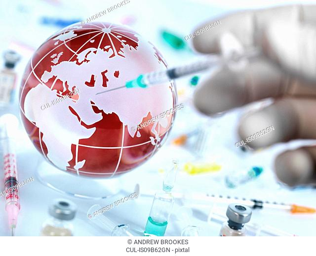 Doctor injecting globe with vaccine to illustrate a cure for a global pandemic