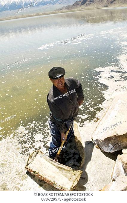 A friendly Kazakh man works in a salty lake