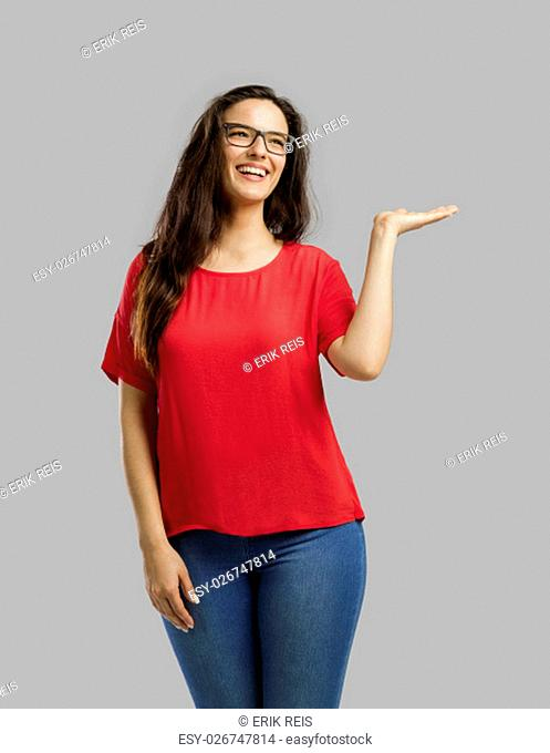 Lovely happy woman showing something on her hand, isolated over white background