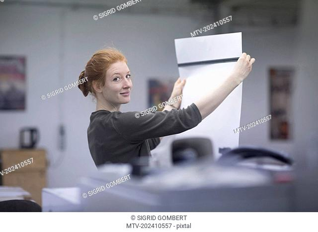 Portrait of beautiful worker measuring printouts with ruler