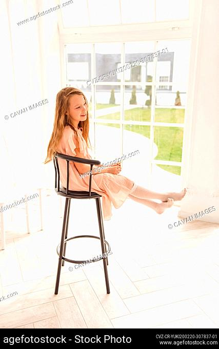 girl sitting in a high chair by the window for Easter