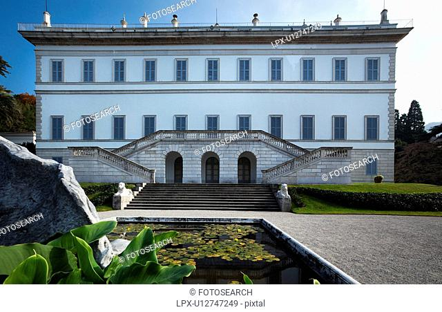 Facade of Renaissance Villa Melzi with steps to terraced bilateral stairway, flanked by lion statues, grassy slopes and fountain with waterlilies on sunny...