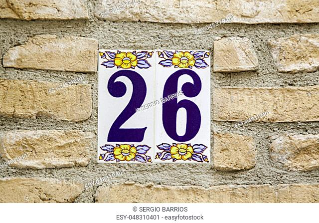 Number sixteen on the wall of a house, detail of the number of information, address