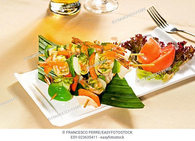 fresh and colorfull grilled shrimps and vegetables skewers on a palm leaf , thai style