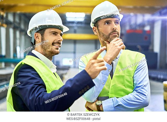 Two managers wearing protective workwear talking in factory