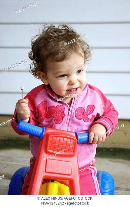 Toddler girl playing on a plastic tricycle
