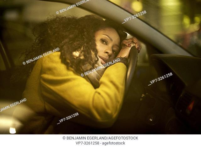 woman leaning on steering wheel, resting inside car, in Munich, Germany