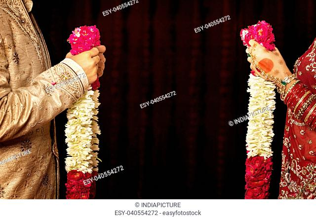 Close-up of bride and groom holding garlands