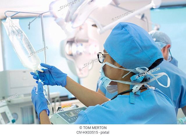 Female anesthesiologist preparing IV drip in operating room