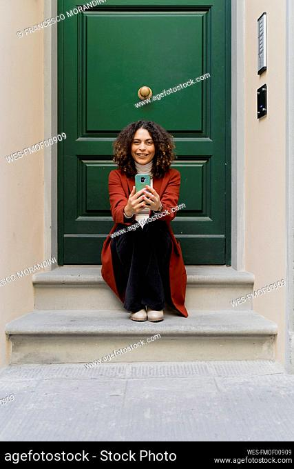 Portrait of smiling woman with smartphone sitting on front stoop