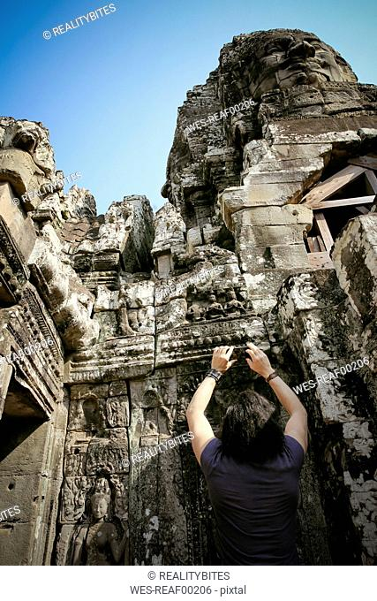 Cambodia, Angkor Wat, Angkor Thom, Bayon temple, tourist taking cell phone picture
