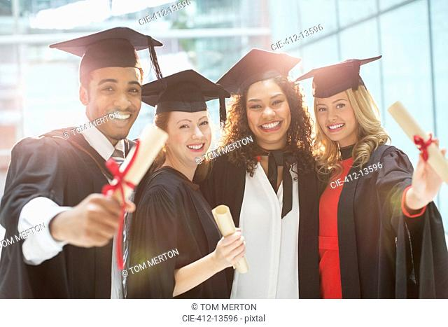 Graduates smiling with diploma