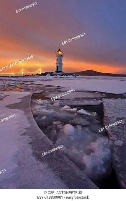 Winter landscape with a view of the lighthouse, iced sea and nig