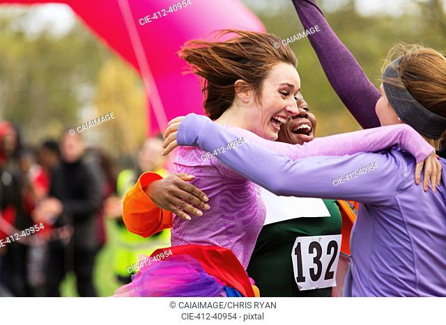 Enthusiastic female runners finishing charity run, celebrating