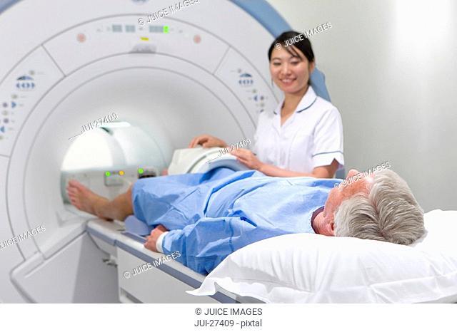 Radiologist helping patient with MRI scanning machine