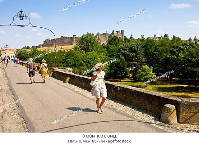France, Aude, Carcassonne, Medieval city listed as World Heritage by UNESCO, woman walking on the Old Bridge which crosses the river Aude