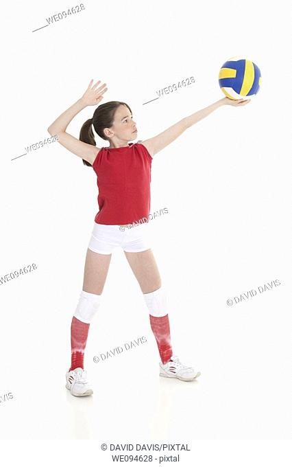 Cute Caucasian girl serving the ball in volleyball