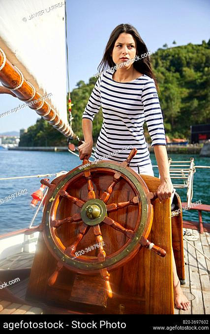 Young woman with sailor clothes, Helm, Sailboat, Pasaia, Gipuzkoa, Basque Country, Spain, Europe