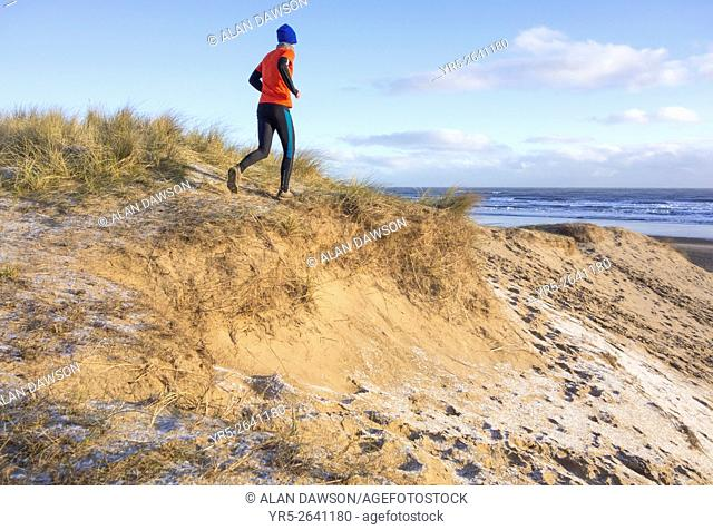 Seaton Carew, north east England, United Kingdom, March 2016. Mature runner running on frost covered sand dunes on Seaton Carew beach at sunrise