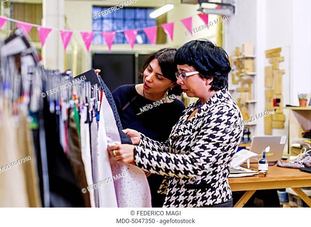 Entrepreneur Zoe Romano, the first woman in Italy to oper a fab lab (fabrication laboratory), talking to an assistant about some cloth samples in her We Make...