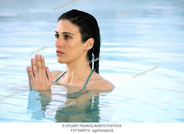 Woman in water, hands clasped